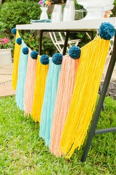 Colorful yarn banner perfect for a summertime party and displaying on the drink station table. See more from this Grad Party on Mint Event Design www.minteventdesign.com