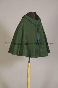 Short cape, ca. 1860 American. Medium-dark green wool twill with matching soutache embroidery & bluish tassels, half circular hip length, pointed decorative hood with tassels on each side throat & CB&showing darker green silk lining, all edges with border of embroidery in grape vine pattern,3 hook & eye clasps. - http://theebonswan.blogspot.com