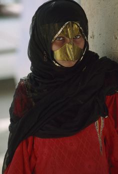 Oman | Portrait of a masked young Bedouin woman of the Wahiba al Wahiba tribe. She is attending a livestock auction