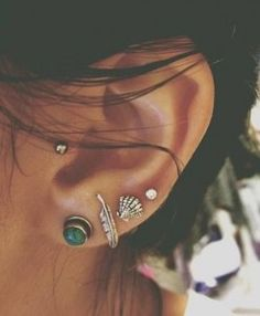 I adore these piercings! I love the earrings too.  The green one, the feather, and the shell are adorable together.  I must get my tragus pierced!