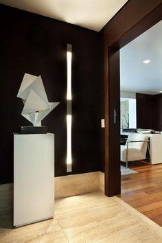 Hall de entrada com papel de parede na cor berinjela, iluminação embutida e…