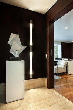 Hall de entrada com papel de parede na cor berinjela, iluminação embutida e escultura. Decoração contemporânea e sofisticada. Projeto de reforma em design de interiores para apartamento de 180 m2 em Moema, São Paulo.
