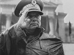 Tito salutes parading troops, tanks and artillery on a rainy day in Belgrade. Behind him is the Yugoslav Assembly building where his coffin was on view after his death.