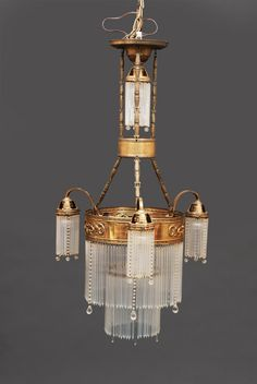 An Art-Nouveau ceiling light  C. 1900. 5 lamp holders. Brass ring with matfinished glass bars and glass balls. Electrified. H. ca. 105 cm, diameter ca. 60 cm.