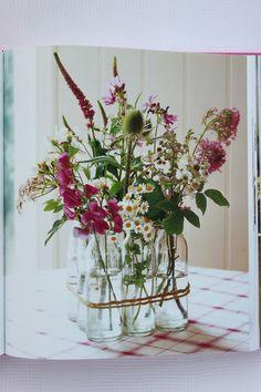 tie 9 vintage milk bottles together with twine to make floral arrangement vase