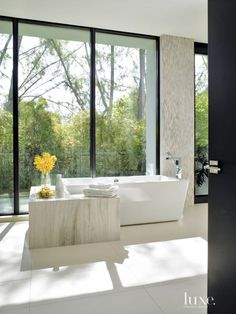 A vein-cut-limestone surround in the master bathroom integrates with a Produits Neptune tub from Tubs and More. The tilework, including the surround, the Italian porcelain flooring and Daltile's stone cladding on the walls, is by Scarsdale Tile & Carpet. Bamboo foliage outside softens the modernity inside and allows for a glass window wall, from A-Christian Glass, while maintaining privacy.