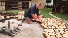 Martin Tyciak built this gorgeous cordwood patio-terrace at his home in Slovakia . Here the 2 inch cordwood slices are being hammered into place so they are level. The base of gravel had already been tamped to make a firm and level foundation.