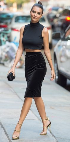 Emily Ratajkowski gave her summery look a dash of fall-ready fusion with a black sleeveless turtleneck Tanya Taylor crop top and a black slit pencil skirt that she styled with a severe topknot and gold sandals.