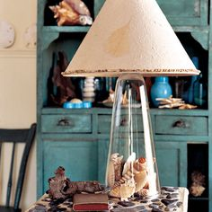 To make this lamp, use an antique chemistry funnel for a base (or a clear glass lamp with an open base) and fill with seashells. Thread a lamp wiring kit through the opening, and top with a shade adorned with miniature shells.