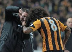 Tom Huddlestone's hair is snipped on the pitch by physiotherapist Rob Price after ending his lengthy goal drought. Football Rivalries, Hull City, Pitch, Goals, Group, Sports, Hair, Hs Sports, Sport