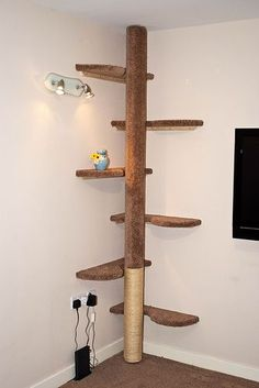 Hand made cat tree. six curved shelves and central pole to climb up, bottom covered in sisal rope for claw removing. The urn on the tree is wee Clawdius, he is the first to go on the cat tree :)