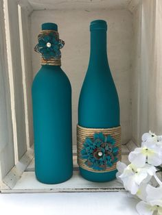 Teal chalk painted wine bottles with twine and metal flowers Blaugrün Kreide bemalte Weinflaschen, 2 Liquor Bottle Crafts, Recycled Wine Bottles, Wine Bottle Art, Painted Wine Bottles, Diy Bottle, Crafts With Bottles, Beer Bottle, Wine Bottle Centerpieces, Diy Centerpieces