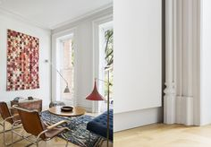 In the main living room, a vintage tapestry hangs with a wall-mounted Johan Petter Johansson triplex lamp from 1919 (left). The Bucks found the two Marcel Breuer S35 chairs on the street during the renovation. The minimalist reveal detail against the crown molding (right).