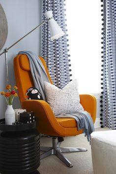 This is a nursery, but I would totally love this as my office! --> Blue & orange boy's nursery design with blue walls painted Para Paints Oxford, orange Ikea Arvika Swivel Chair, glossy black ribbed accent table and white & blue geometric pattern curtains.    Para Paints Oxford. I LOVE THE CHAIR!!