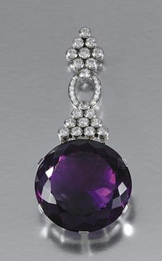 AMETHYST AND DIAMOND PENDANT, EARLY 20TH CENTURY Centring on a circular faceted amethyst, to an articulated surmount collet- and claw-set with circular- and single-cut diamonds, to a fancy link chain, length approximately 440mm, drop detachable from surmount.