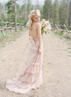 blush pink wedding dress, photo by Laura Murray http://ruffledblog.com/devils-thumb-ranch-wedding #weddingdress #weddinggown #pinkweddingdress