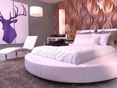 Too Hip to Be Square: David covered an accent wall in sculptural, laser-cut mahogany to create a dramatic backdrop for the room's nightclub-inspired round bed. Minimal twin headboards, covered in the same sleek, white vinyl as the rest of the bed, provide a comfortable spot for lounging without visually competing with the focal wall.