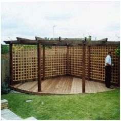 corner pergola: paved not with decking. Climber plants covering the woods & seating area/chimnea.