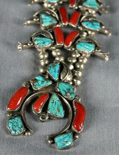Turquoise & Coral Squash Blossom Necklace with Earrings by Felicita Eustace. Note the carved turquoise stones and stamped curved silver leaf  typical of Eustace Family work.