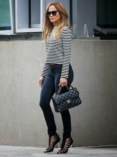 Singer Jennifer Lopez dressed up her casual jeans and long-sleeve tee look with black L.A.M.B. Falyn Sandals and a Chanel handbag.