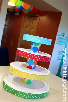 Cupcake Tower is made out of cardboard cake circles, soup cans, ribbon and wrapping paper... Carnival party idea.
