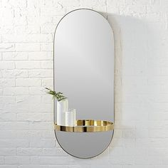 Shop caplet oval mirror with shelf.   Luxe oval looking glass with half circle shelf is a sight to behold.  Designed by Mark Daniel, brass-colored stainless steel frame elegantly edges elongated structure for a fine finish.