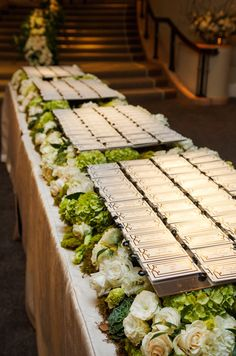 Guests' place cards are displayed on a on a bed of white roses and green hydrangeas.