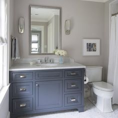 Bathroom with blue-gray vanity, framed mirror and wall scones. Small neutral bathroom idea