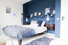 A bedroom in blue with many little shelves above the bed.