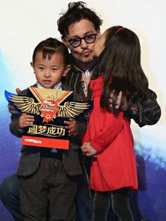 This melts our hearts! Johnny Depp hangs with two adorable kiddos at the 'Transcendence' press conference in Beijing, China.