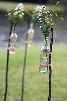 DIY super easy, super inexpensive and just FAB!!!  Gather bottles, use twine or raffia to tie them on sticks you gather.  Find as straight sticks as you can find and whittle the ends down to a point.  Push them into the ground then tie on your bouquets.