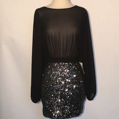 Sultry mini evening,club dress. Sultry black chiffon bodice and sleeves. Skirt made of sequins in iridescent black.  Sheer is in right now. Has crisscross back and cutout. Xtaran Dresses Maxi