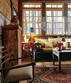 A wicker couch, peeled coffee table and ceramic vases create a romantic, Old World setting on the sleeping porch.