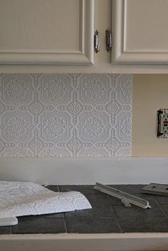 Ceiling tile patterned wallpaper for kitchen backsplash. (Can, possibly, be painted?)