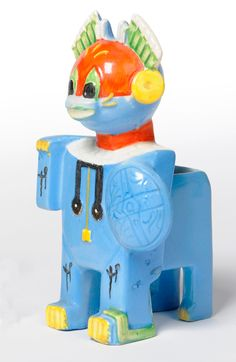 """Louis Wain"" Futurist Cat, design registered 1914, modelled standing holding a shield, painted blue, yellow, green and black, printed and moulded marks, Louis Wain, Made in England, Reg. No. 638312, 15cm (re-painted and restored)."