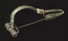 "B2461. A LATE ROMAN FIBULA, ca. 3rd-4th century. The spring type bronze fibula with catch plate tail looped back and wrapped around. 2.8"". Fine example."