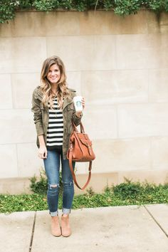 cute fall outfit idea, how to wear a green military jacket styled with black and white stripes,cognac booties and brown leather sole society bag