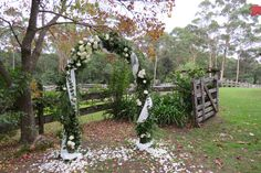Flowers and lush foliage with soft draping on the arch for this country garden wedding. Elegance in a rustic setting. Garden arbor , rural setting