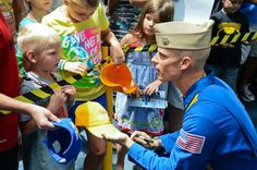 PENSACOLA, Fla. (June 19, 2013) – U.S. Navy Flight Demonstration Squadron, the Blue Angels, Left Wing pilot #3 Lt. Cmdr. Nate Barton autographs a young fan's hat at the National Naval Aviation Museum on board Naval Air Station Pensacola.