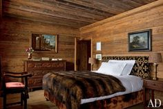 Studio Peregalli - The master bedroom of a Saint Moritz, Switzerland home is lined with pine and features lamps by Studio Peregalli and a 17th c. Italian commode surmounted by an 18th c. capriccio.