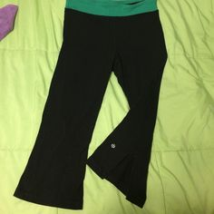 Cute Lululemon Crop Workout Pants Super soft stretchy material!! Green waste band, the capris are slit at the bottom of the pant, SO cute with a cute pair of sneakers!!!! Small slice in the back ground from cycling and getting caught on the peddle. No big deal!!! Make an offer if you think it's so egregious! lululemon athletica Pants Track Pants & Joggers
