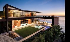 Home Design: Relaxing Black Lounge Chairs Paired With Contemporary House Architecture Plus Blue Patio Led Light Plus Glass Wall Design: Sophisticated Modern House Designs with Flat Roof