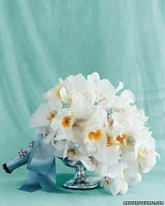 Martha envisioned Jessica's bouquet with two kinds of orchids and white and blue pearlescent beads. The stems were bound with double-faced blue satin ribbon, which was tied in a bow and embellished with rhinestone buttons