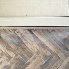 Subway tile shower with herringbone wood look tile bathroom floor. Superior Development, Llc. Nashville builder
