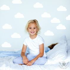 Small white clouds wall decal pattern on a light blue wall in a children's bedroom.
