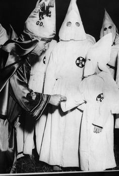 Dr. Samuel Green (left), Grand Dragon of the Ku Klux Klan, greets a small boy dressed in Klansman's robes. The boy was one of many children so dressed to attend the mass initiation. Stone Mountain, Georgia. June 14, 1949. (CSU_ALPHA_1182) CSU Archives/Everett Collection