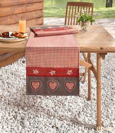 Dieser Tischläufer mit Edelweißmotiv und rot/beige kariertem Grundstoff mit roter und brauner Borde sorgt für typisches Hüttenflair.