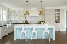 Chic cottage kitchen features a pair of Goodman Hanging Lamps in Antique Brass illuminating a light blue kitchen island topped with white marble fitted with sink lined with white Tolix Counter Stools.