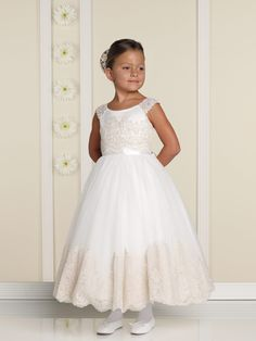 Flower girl. Satin and tulle off-the-shoulder tea-length dress with lace cap sleeves, satin bodice with hand-embroidered lace overlay, satin ribbon waistband and tie back sash, full tulle skirt with matching hand-embroidered scalloped lace trim.