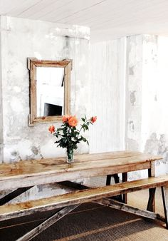 Rustic eclectic dining room with grey and white worn walls, wood rectangular mirror and long wood picnic style table